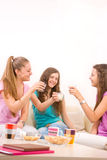 Three young girls having a drink on sofa Stock Images