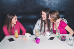 Three young girls having fun in a cafe. Three young girls laughing and having fun in a cafe Royalty Free Stock Image