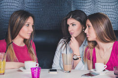 Three young girls having serious conversation Royalty Free Stock Photography