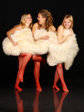 Three young girls hiding behind white fur. Royalty Free Stock Photos