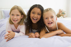 Three Young Girls Lying On A Bed In Their Pajamas Stock Photo