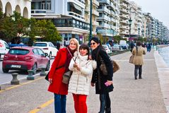 Three young girls make selfy with mono-pod on Leof Nikis Street in Thessaloniki Greece March 2018. Tourists make picture themselve royalty free stock photography