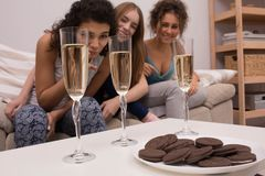 Women in pajamas on sofa. Three young girls making pajamas party. Enjoying with champagne and cookies Royalty Free Stock Images
