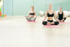 Three young girls meditate in sports gym Royalty Free Stock Photos