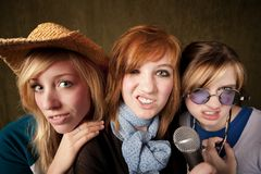 Three Young Girls with Microphone Making Faces Stock Photography