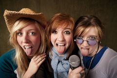 Three Young Girls with Microphone and Tongues Out Royalty Free Stock Photos