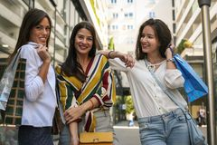 Three young girls poses with bags after shopping. Stock Photo