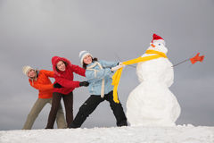Three young girls pull snowman by scarf Stock Photo