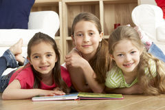 Three Young Girls Reading Book at Home royalty free stock photo