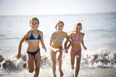 Three young girls running out of the sea Stock Photos