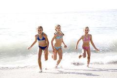 Three young girls running out of the sea Royalty Free Stock Image