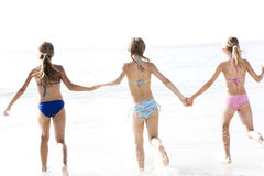 Three young girls running into the sea Royalty Free Stock Photo