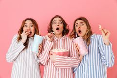 Three young girls 20s wearing colorful striped pyjamas expressin. G excitement or thrill while watching movie at slumber party and eating pop corn isolated over Stock Photo
