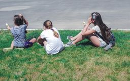Three young girls sitting in grass, rear view stock photography