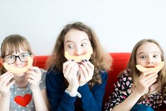 Three young girls sitting on red sofa and eating yellow melon royalty free illustration