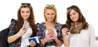 Three young girls standing with luggage at the airport and looking at phone. A trip with friends Stock Photography