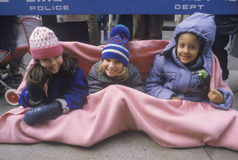 Three young girls staying warm while waiting for a parade, NY Stock Photo