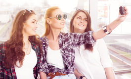Three young girls in sunglasses doing selfie on the computer tablet Royalty Free Stock Image