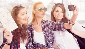 Three young girls in sunglasses doing selfie on the computer tablet Royalty Free Stock Images