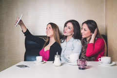 Three young girls taking selfie in a cafe Royalty Free Stock Photos