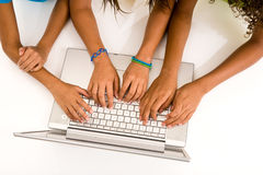 Three young girls typing on a laptop Royalty Free Stock Photo