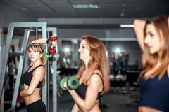 Three young girls workout in the gym Royalty Free Stock Image