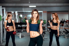 Three young girls workout in the gym Royalty Free Stock Photos