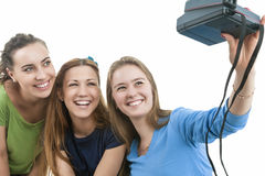 Three Young Happy caucasian Females With Photocamera Taking Self. Ie Photographs. isolated over White Background. Horizontal Image Orientation Royalty Free Stock Images