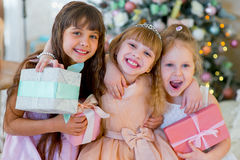 Three young happy girls with Christmas gifts. Three young happy girls in a dress sitting on the bed with Christmas gifts royalty free stock image