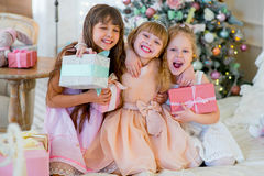 Three young happy girls with Christmas gifts. Three young happy girls in a dress sitting on the bed with Christmas gifts royalty free stock photo