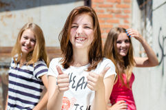 Three young happy teenage girls showing thumb up. Three young happy smiling & looking at camera girl friends showing thumb up at brick wall Royalty Free Stock Photo