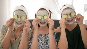 Three young happy women with face masks spending time at spa resort. Friendship and wellbeing concept, health beauty
