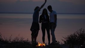 Three young hipster friends chilling on seaside with bonfire making marshmallows with a fire and chatting in cozy summer. Evening stock footage