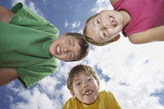 Three Young Kids Bending Down Against Sky Royalty Free Stock Images