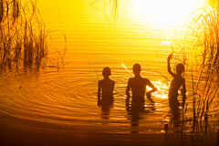Three young kids fishing on the lake at sunset. Vivid golden colors Royalty Free Stock Photo