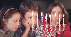 Kids watching hanukka candles burning. Three young Kids watching hanukka candles burning stock footage