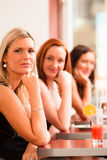 Three young ladies with a drinks Royalty Free Stock Images