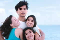 Three young ladies hugging tall handsome young man by lake. Tall young biracial men hugging three laughing young women outside  with ocean horizon in background Royalty Free Stock Images