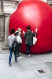 Three young ladies interact with a giant red ball Stock Photo