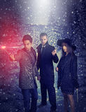 Three young magicians holding a magic wand during a snowy night. Three magicians holding a magic wand Royalty Free Stock Images