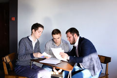 Three young male programmers communicate using tablet while sitt Stock Photo