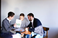 Three young male programmers communicate using tablet while sitt Stock Image