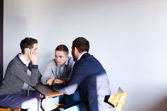 Three young male programmers communicate using tablet while sitt Royalty Free Stock Photo