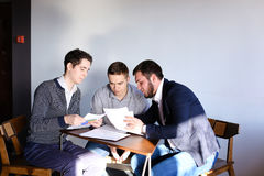 Three young male programmers communicate using tablet while sitt Royalty Free Stock Photos