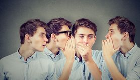 Three young men whispering each other and to shocked astonished guy in the ear. Stock Image