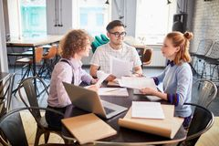 Briefing. Three young managers gathered by table to discuss financial papers and prepare for seminar royalty free stock photo