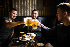 Three young men in casual clothes are smiling and clanging glasses of beer together while sitting in pub Stock Photos