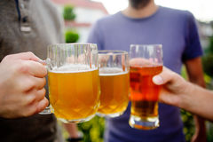 Three young men cheerfully spend time behind a glass of beer Stock Photo