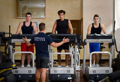 Three young men exercising on treadmills with personal trainer Stock Photos