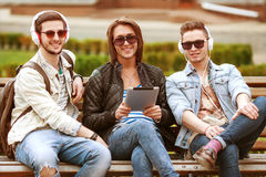 Three young men friends using tablet Stock Photos